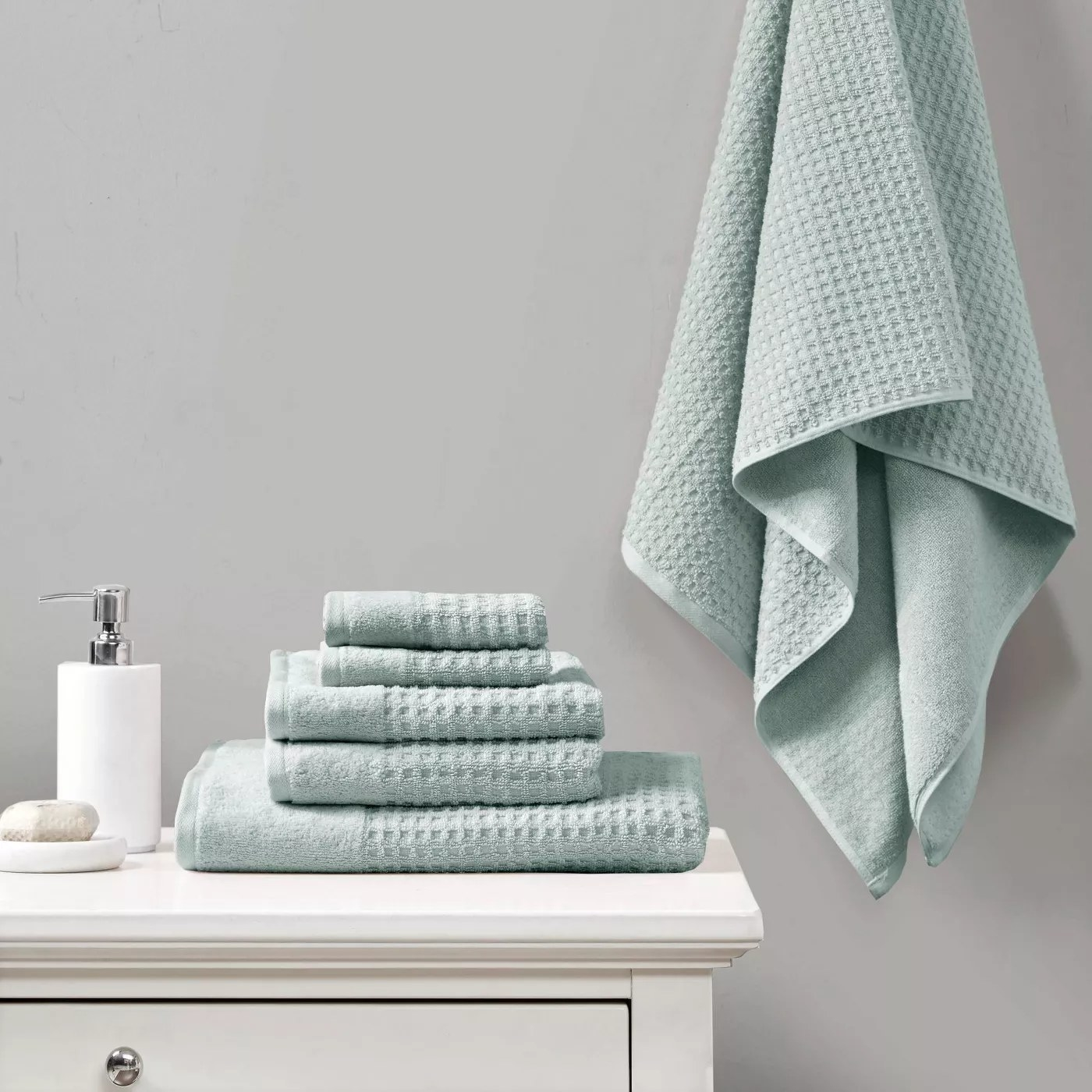 The aqua bath towel set with waffle texture on display in a bathroom