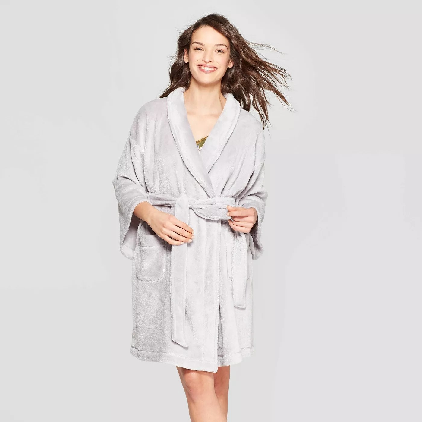A model wearing the plush gray bathrobe with a sash