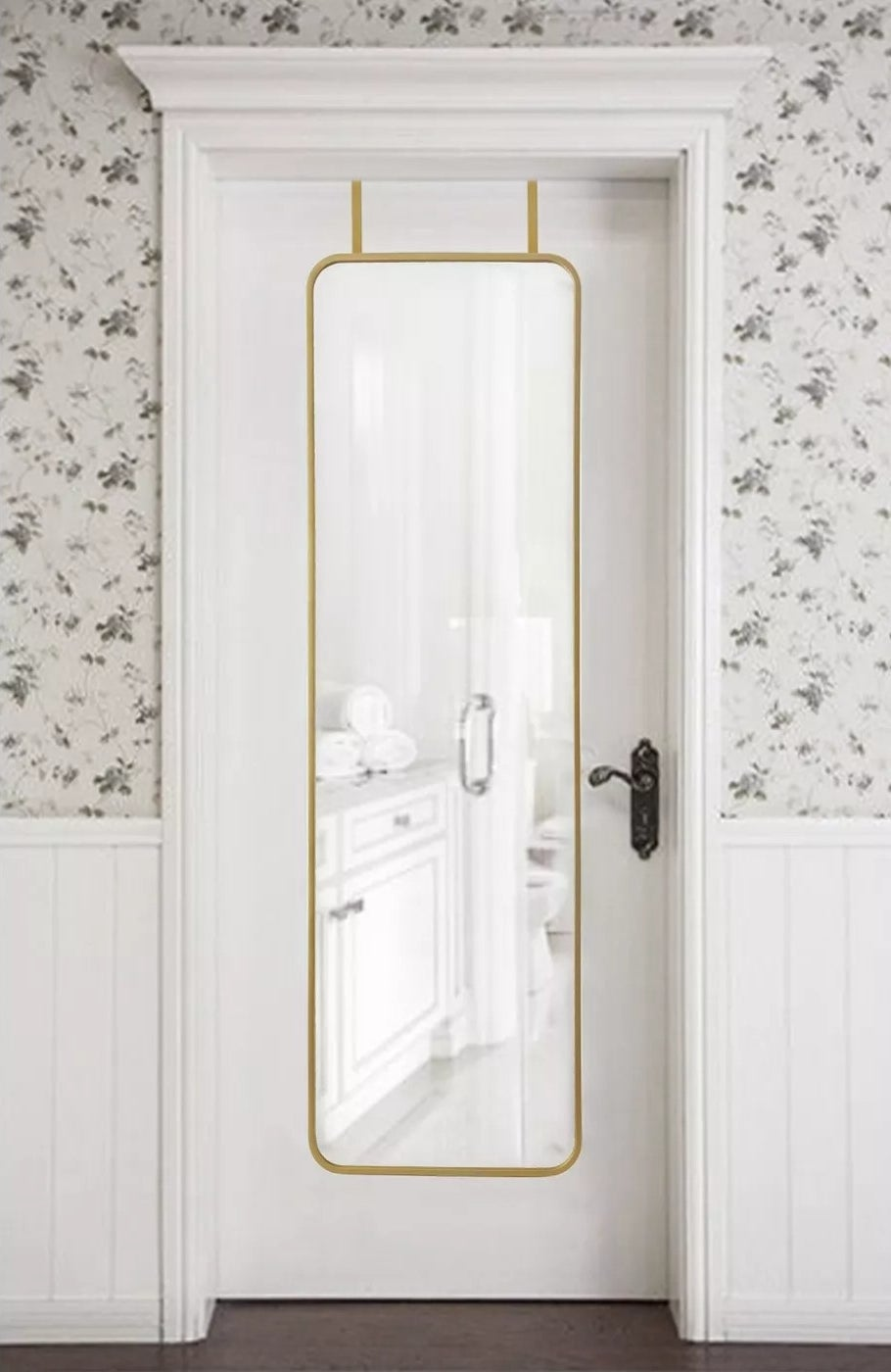 The brass-trimmed mirror with rounded edges hanging on a door