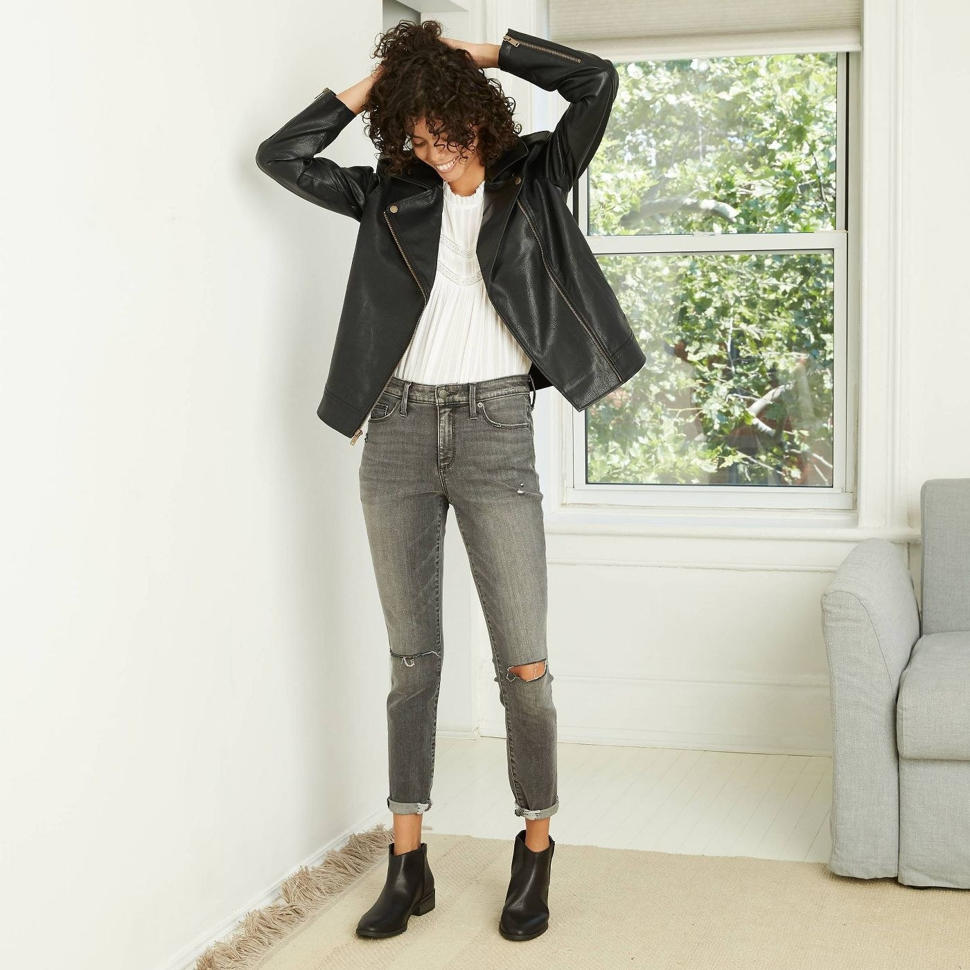 person wearing a faux leather black moto jacket with white t shirt and jeans