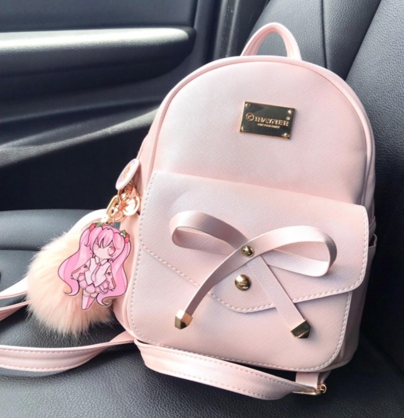 The backpack in pink in the passenger seat of a car