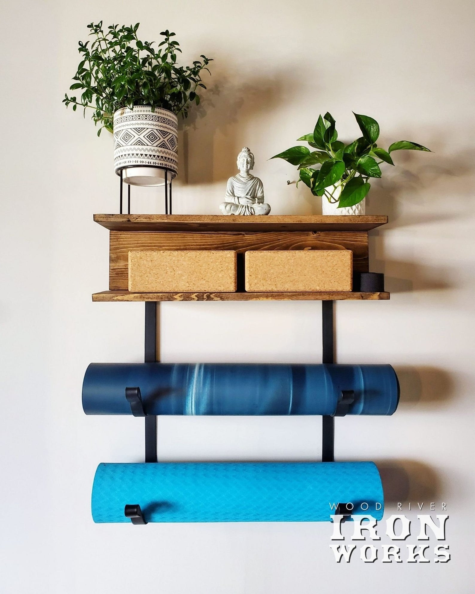 the yoga mat rack with two shelves mounted on a wall with two yoga mats handing from its two racks and two yoga blocks on the shelf