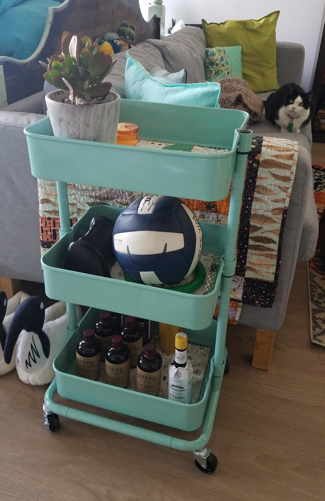 reviewer image of the mint green SONGMICS 3-Tier Utility Cart in a studio apartment with assorted goods in each basket