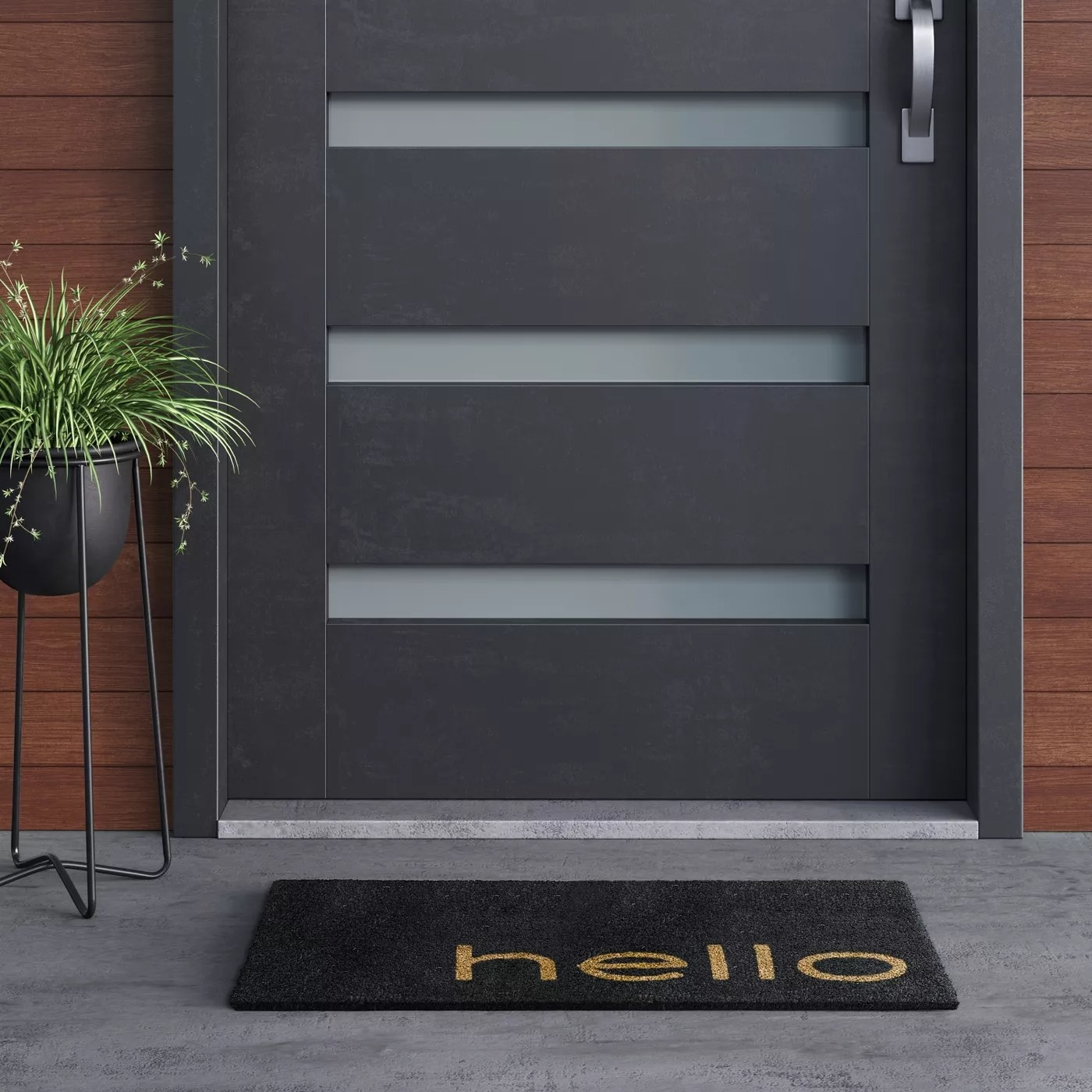 "The black doormat with ""hello"" written on it in tan letters outside a front door"