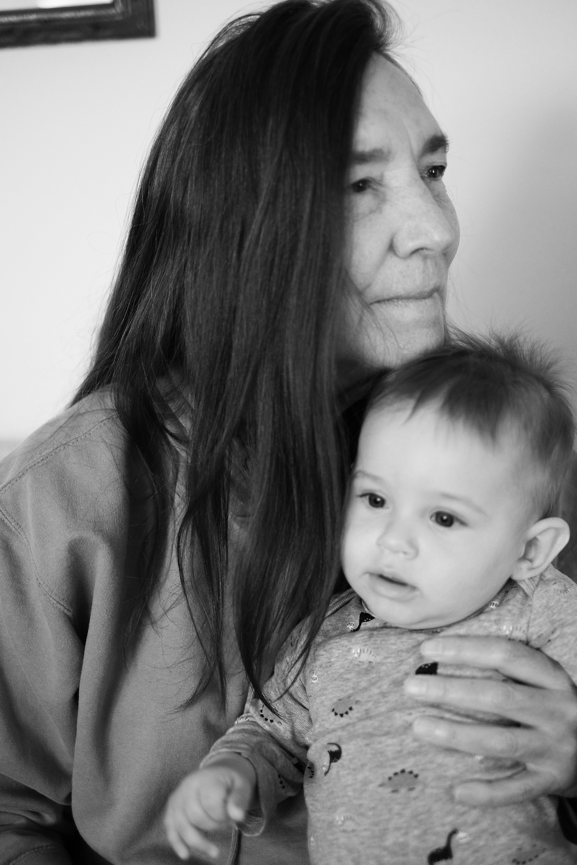 An older woman holds a toddler with her chin on the child's head