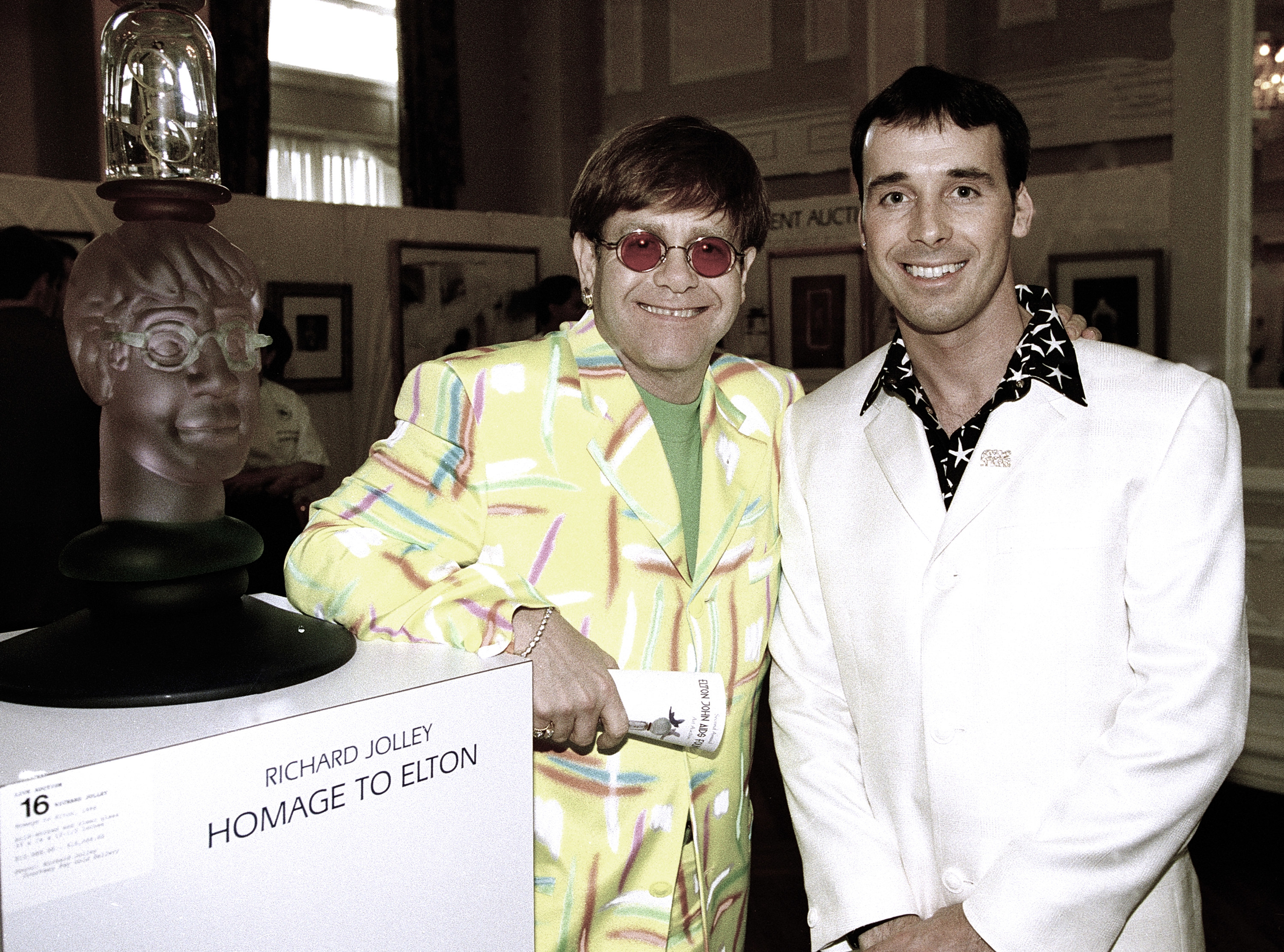 A younger Elton John and David Furnish smiling for a photo next to an art piece dedicated to Elton