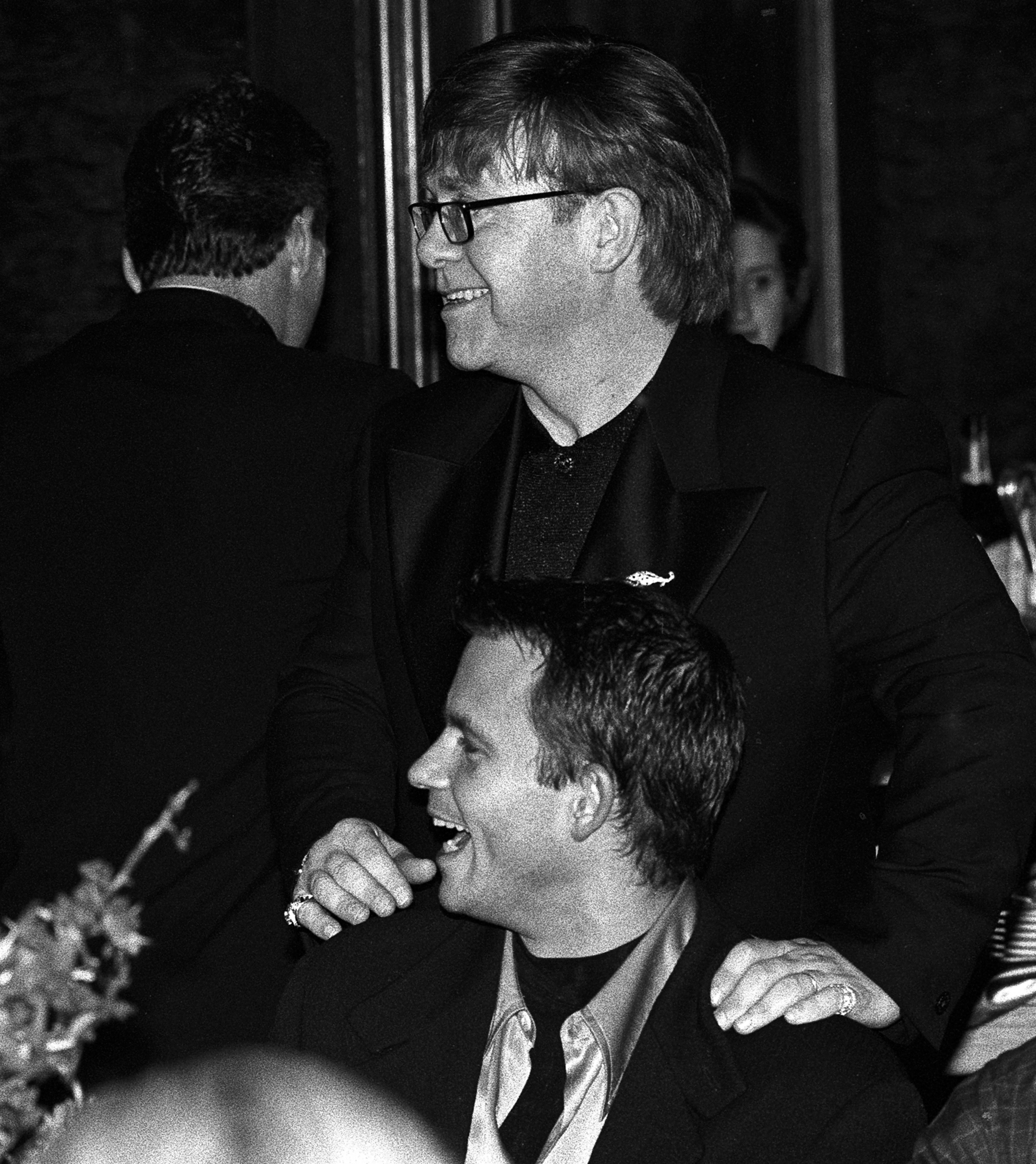 A younger Elton John with his hands on David Furnish's shoulders