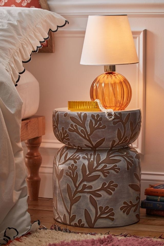 the small ceramic stool being used as a nightstand