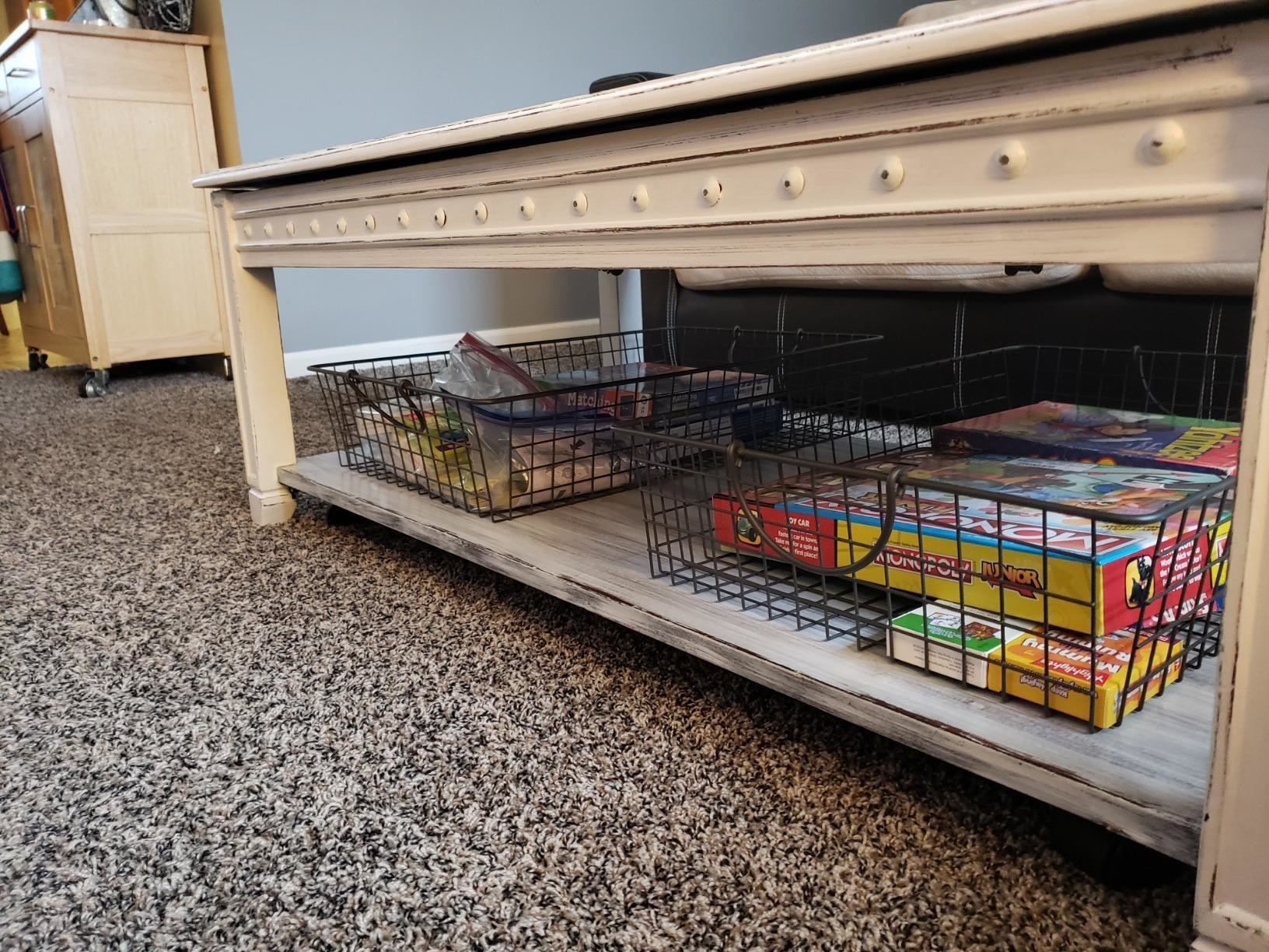 reviewer image of two spectrum stowaway baskets full of boardgames under a coffee table