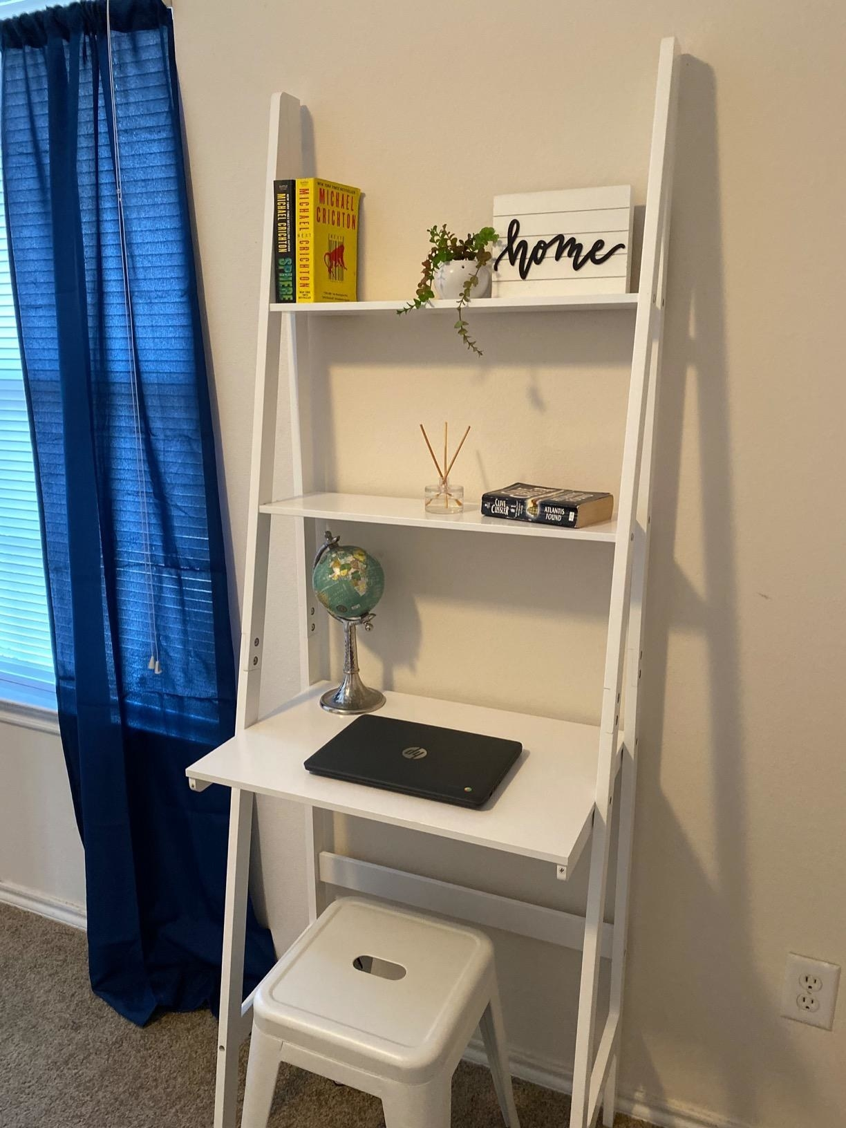 reviewer image of the white itaar three tier ladder bookshelf against a wall