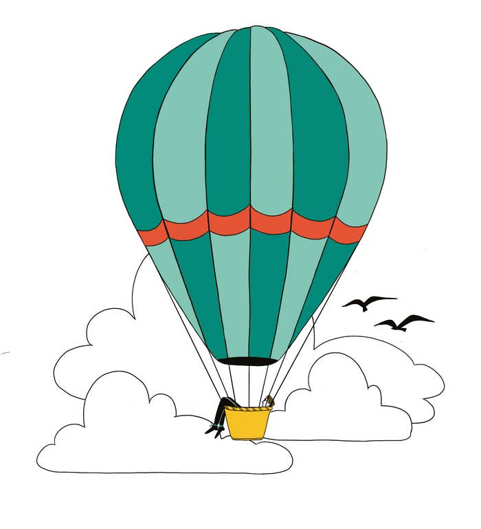 A person floats in a cloudy sky in a hot air balloon, with legs dangling over the side of the basket. Two birds fly next to the balloon.