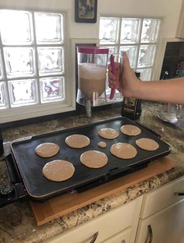 person using the batter dispenser to make pretty evenly sized pancakes on a griddle