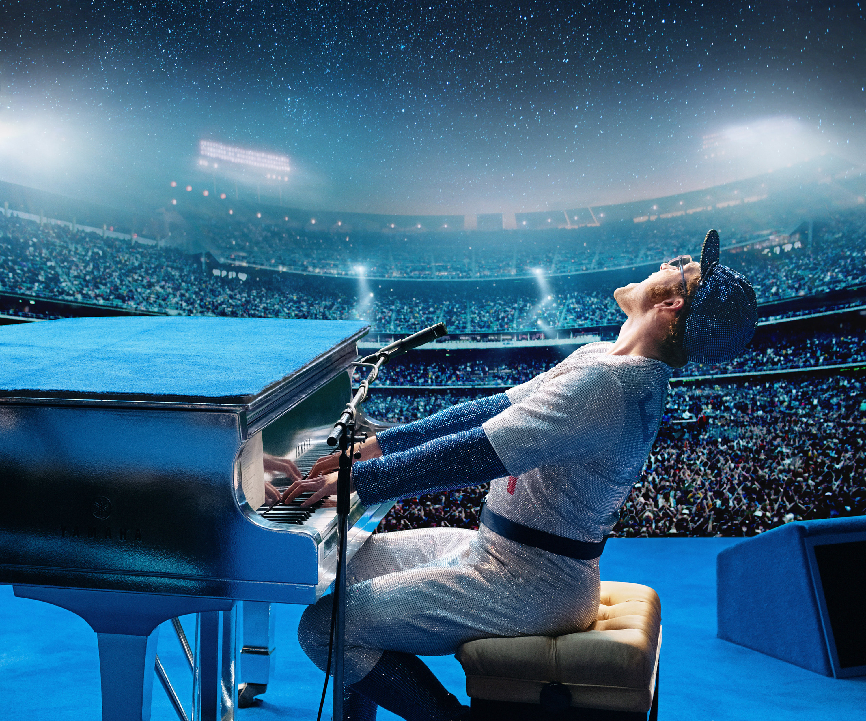 Image from the film Rocketman showing Taron Egerton as Elton John playing the piano in a packed stadium