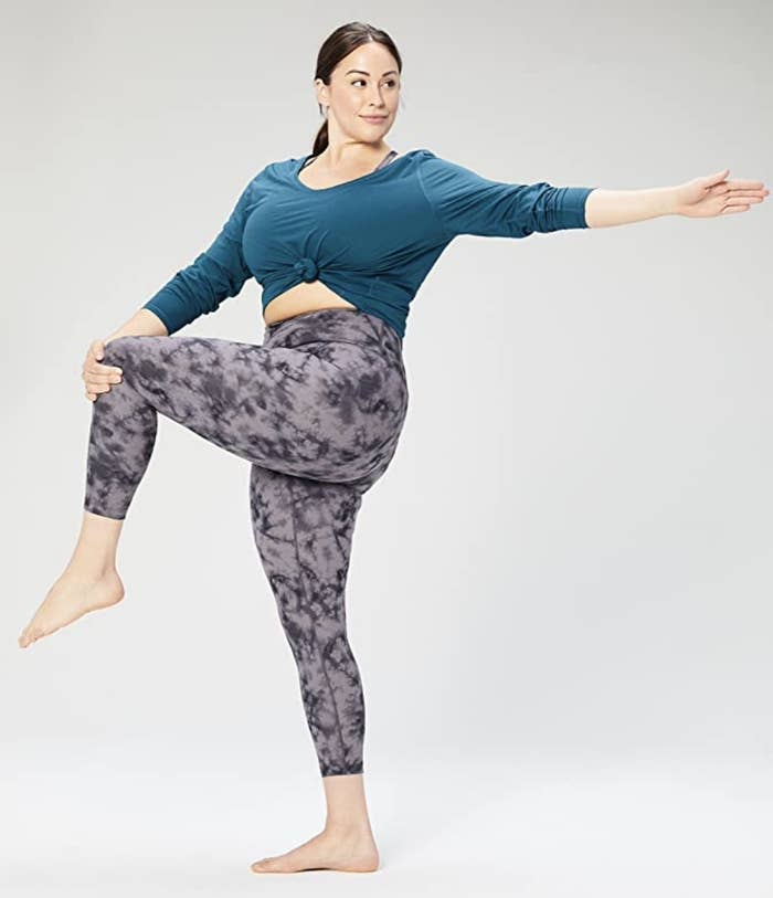 A girl standing and doing a yoga pose in a pair of tie dye leggings