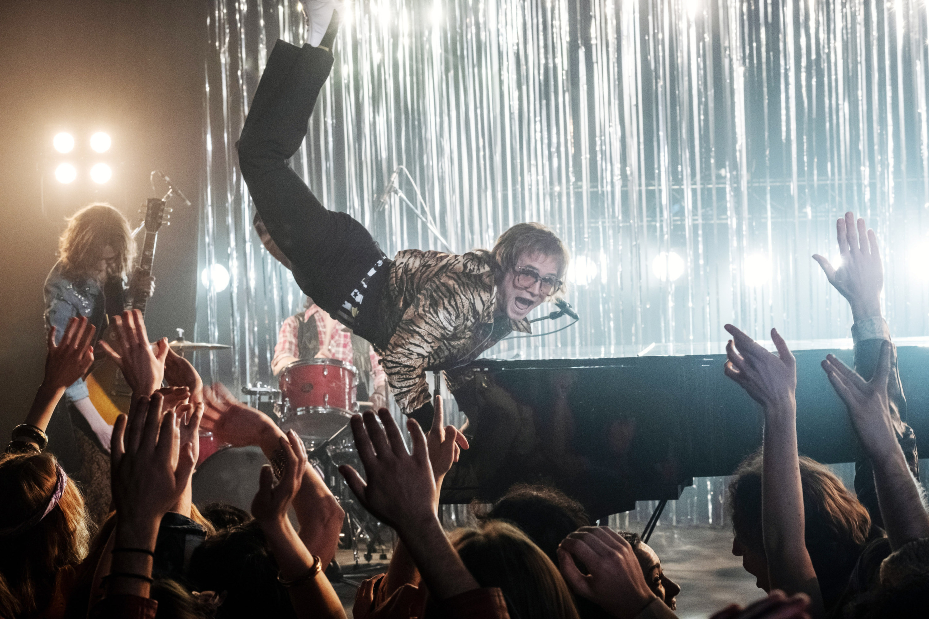 Taron Egerton as Elton John jumping up as he performs for an excited crowd