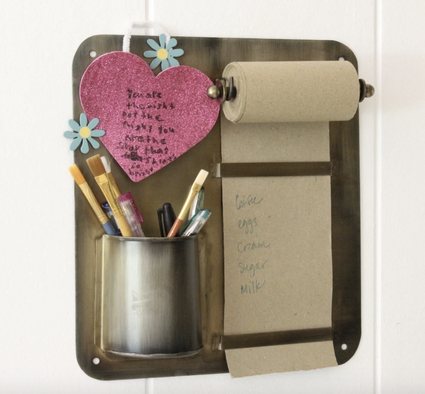 the aged brass note roll and organizer mounted on a wall