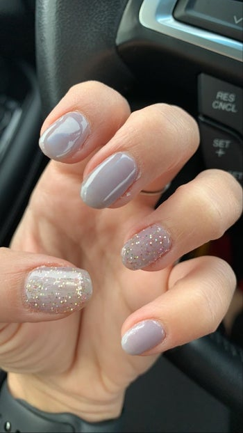 Reviewer with periwinkle nails and glittery white accent nail and thumb nail