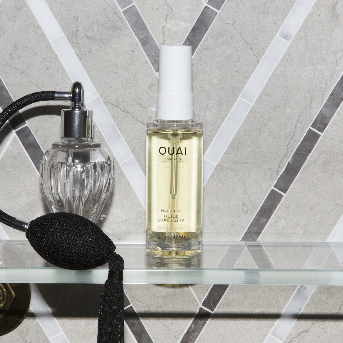 the bottle of hair oil next to a perfume bottle on a countertop