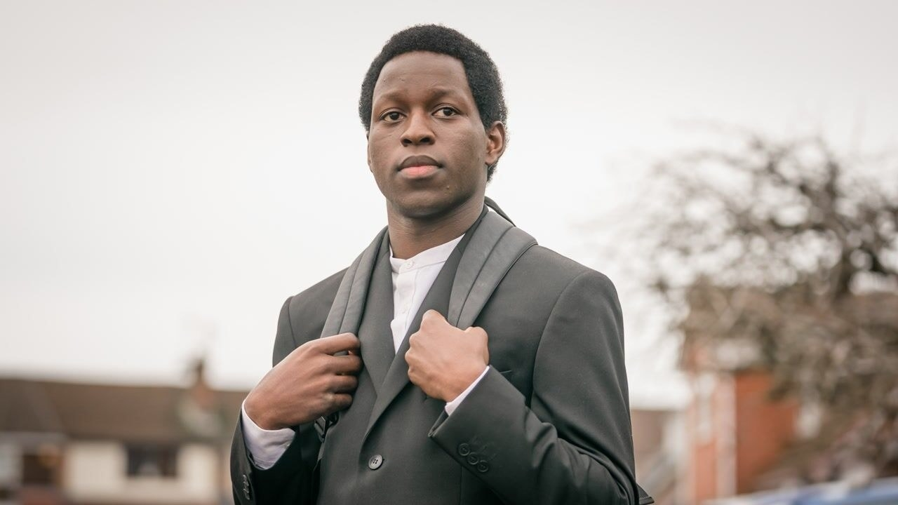 Toheeb Jimoh wearing a suit and backpack as Anthony Walker