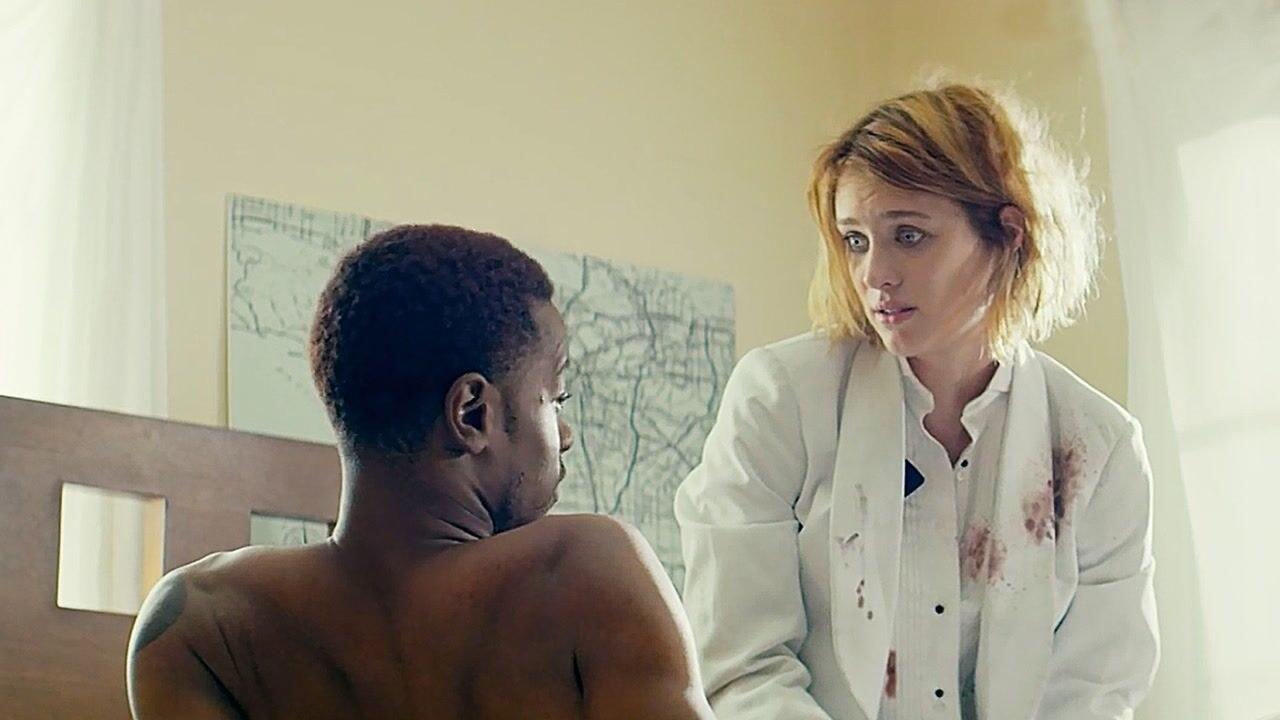 Mackenzie Davis's character wearing a blood-splattered white jacket