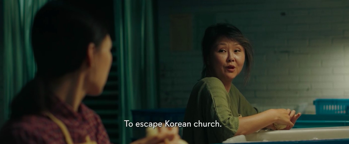 "Monica sitting down at her chicken-sexing job, conversing with her coworker. Text subtitles on image read, ""To escape Korean church."""