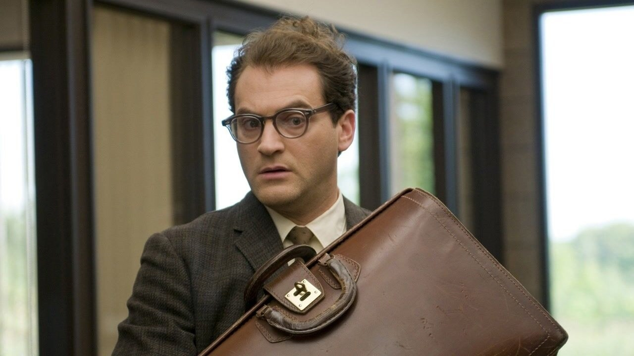 Michael Stuhlbarg's character holding a briefcase