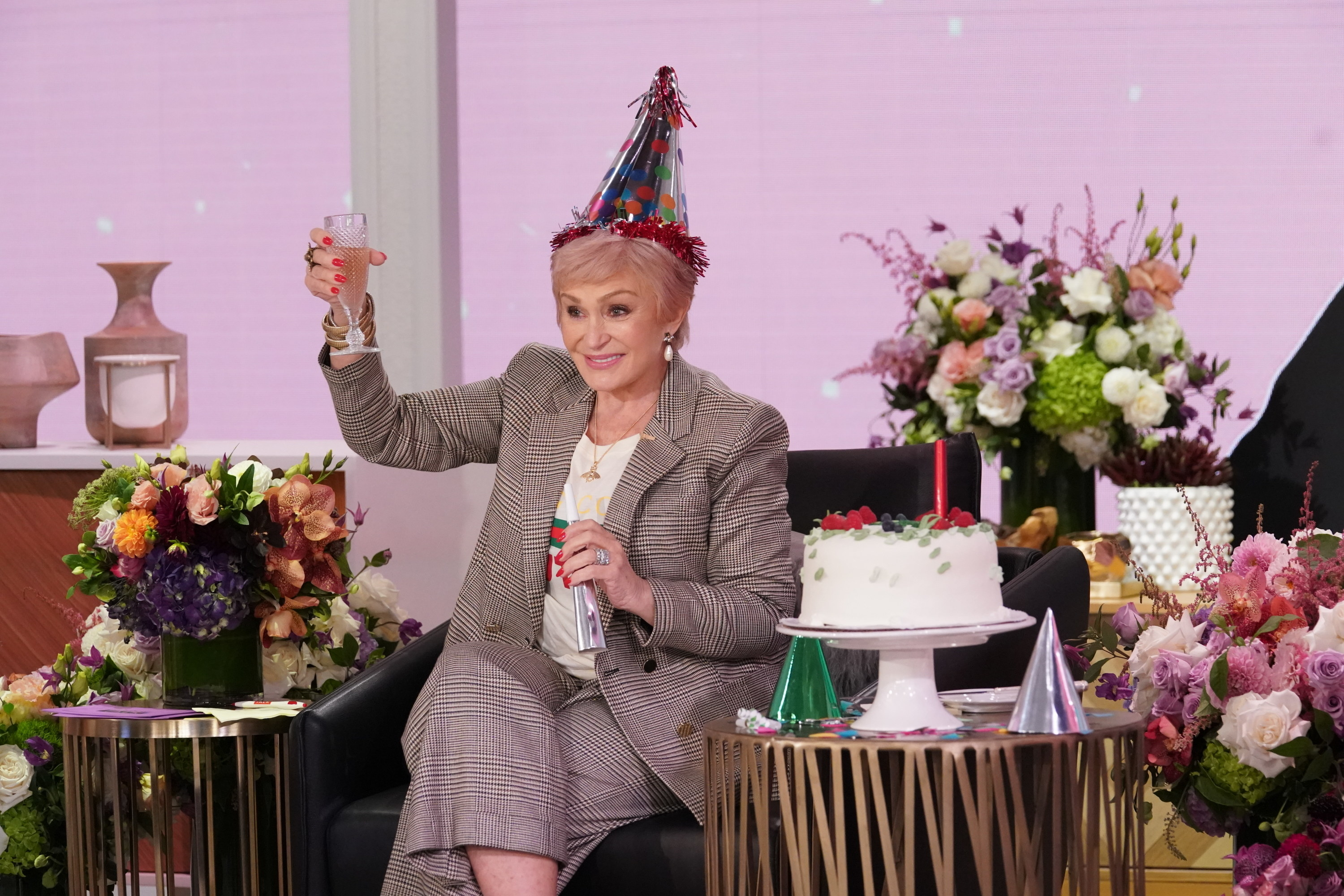 Osbourne wears a party hat and holds up a glass during an episode of The Talk