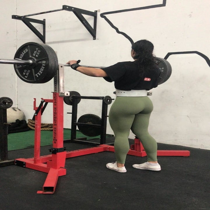 A different reviewer wearing the leggings in green, showing the back while at the gym