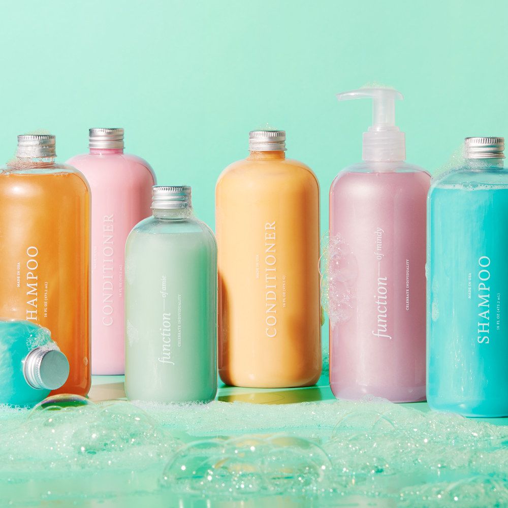 bottles of colorful Function of Beauty shampoos and conditioners in a shower