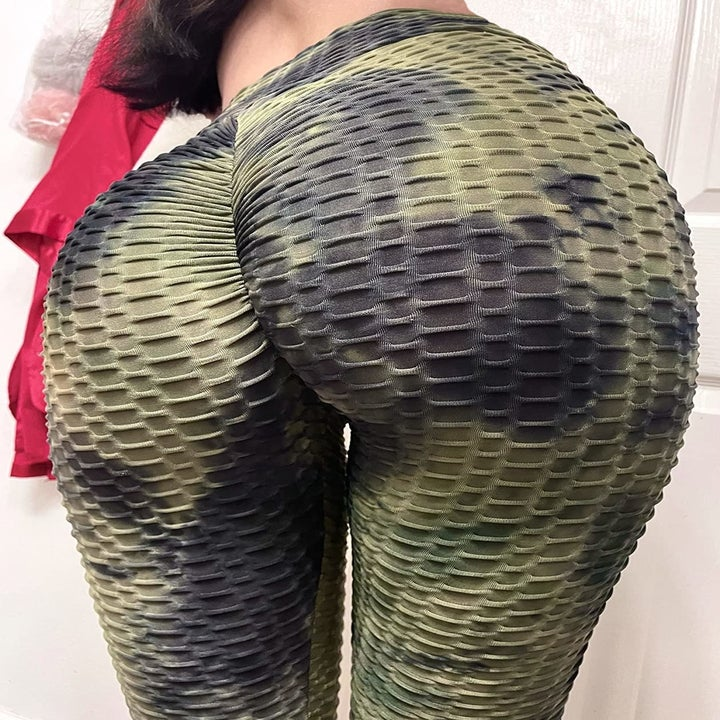 reviewer showing the back view of their green and black textured leggings