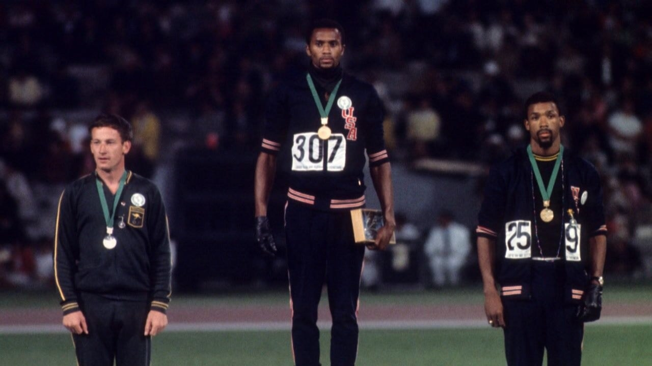 Tommie Smith and John Carlos standing on the Olympic podium with their medals around their necks