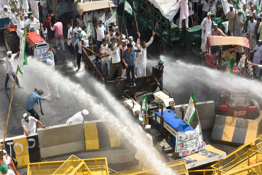Police use tear gas and water cannons to stop farmers from entering New Delhi.