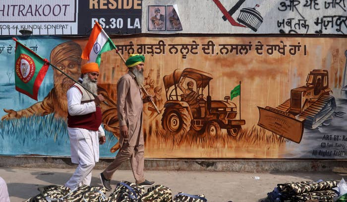Two farmers walk with flags on the 70th day of the protests.
