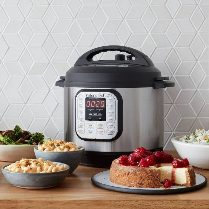 instant pot on table next to pasta, vegetables, and cheesecake