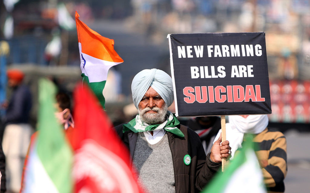 """A protestor holds a sign that says """"New Farming Bills Are Suicidal."""""""