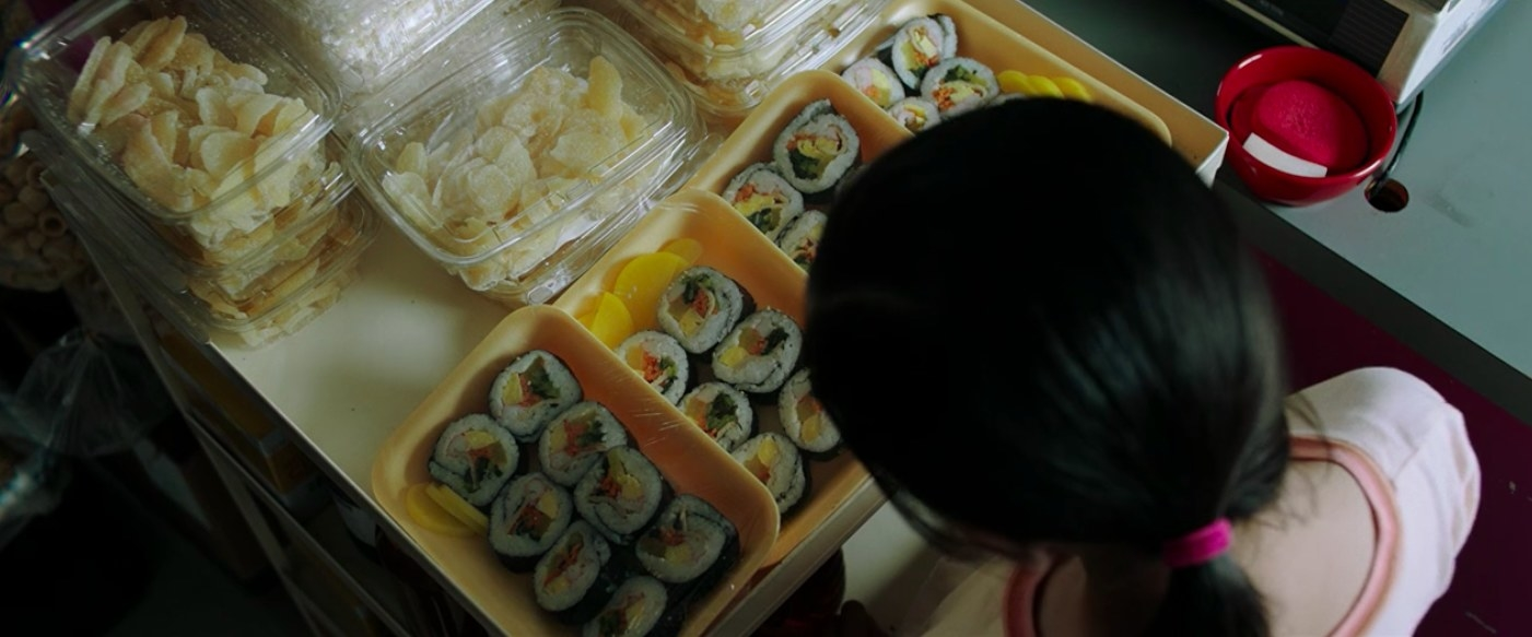 Anne looking at four trays of Korean kimbap.