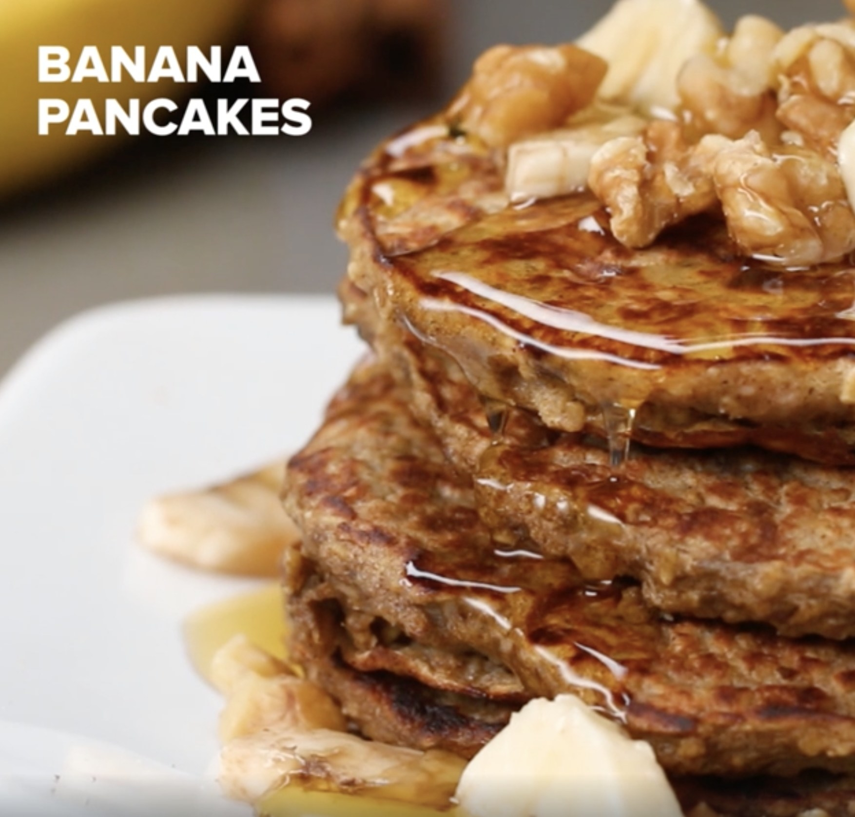 A plate of banana pancakes with syrup and walnuts