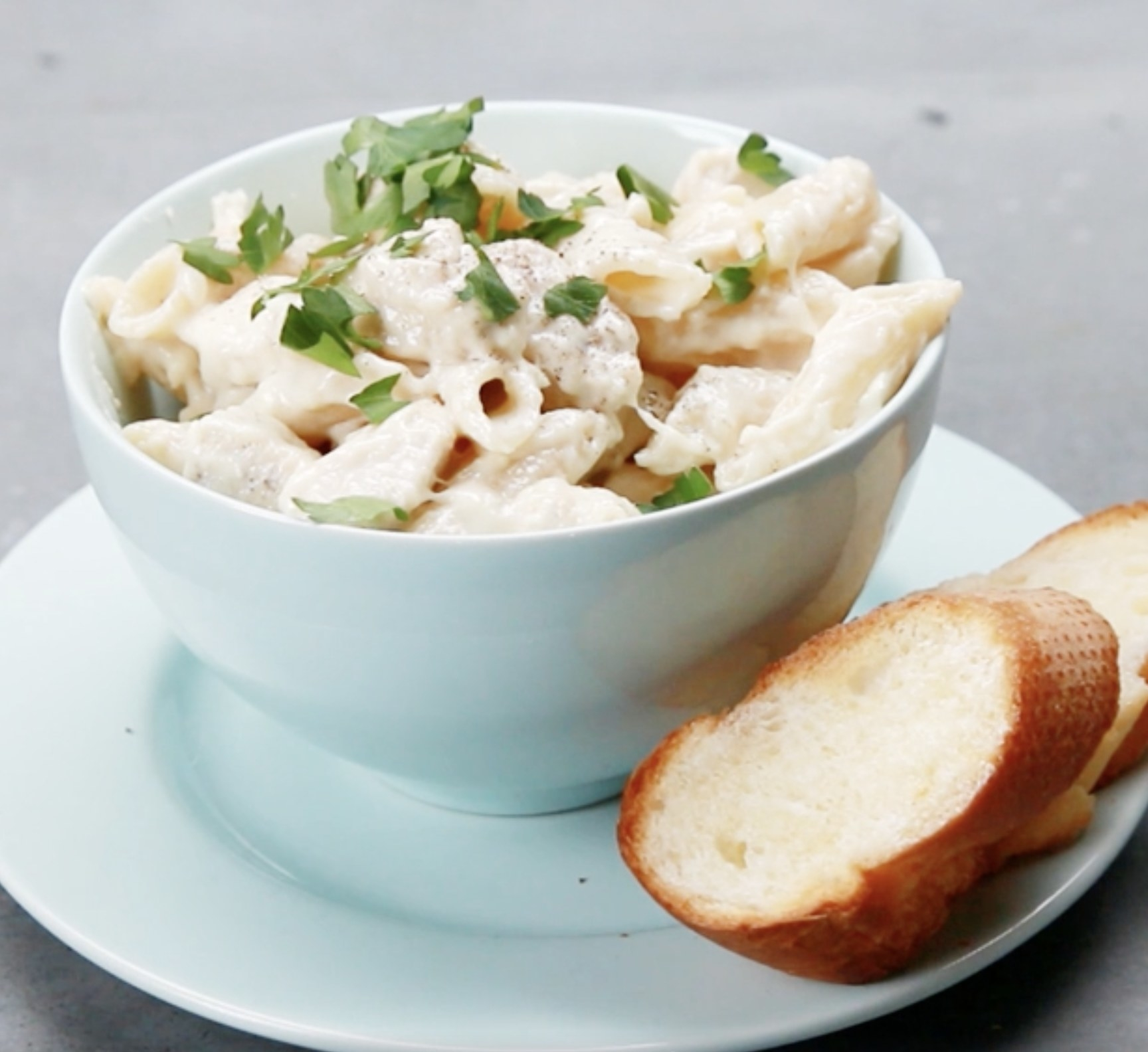 A bowl of chicken alfredo and two slices of french bread