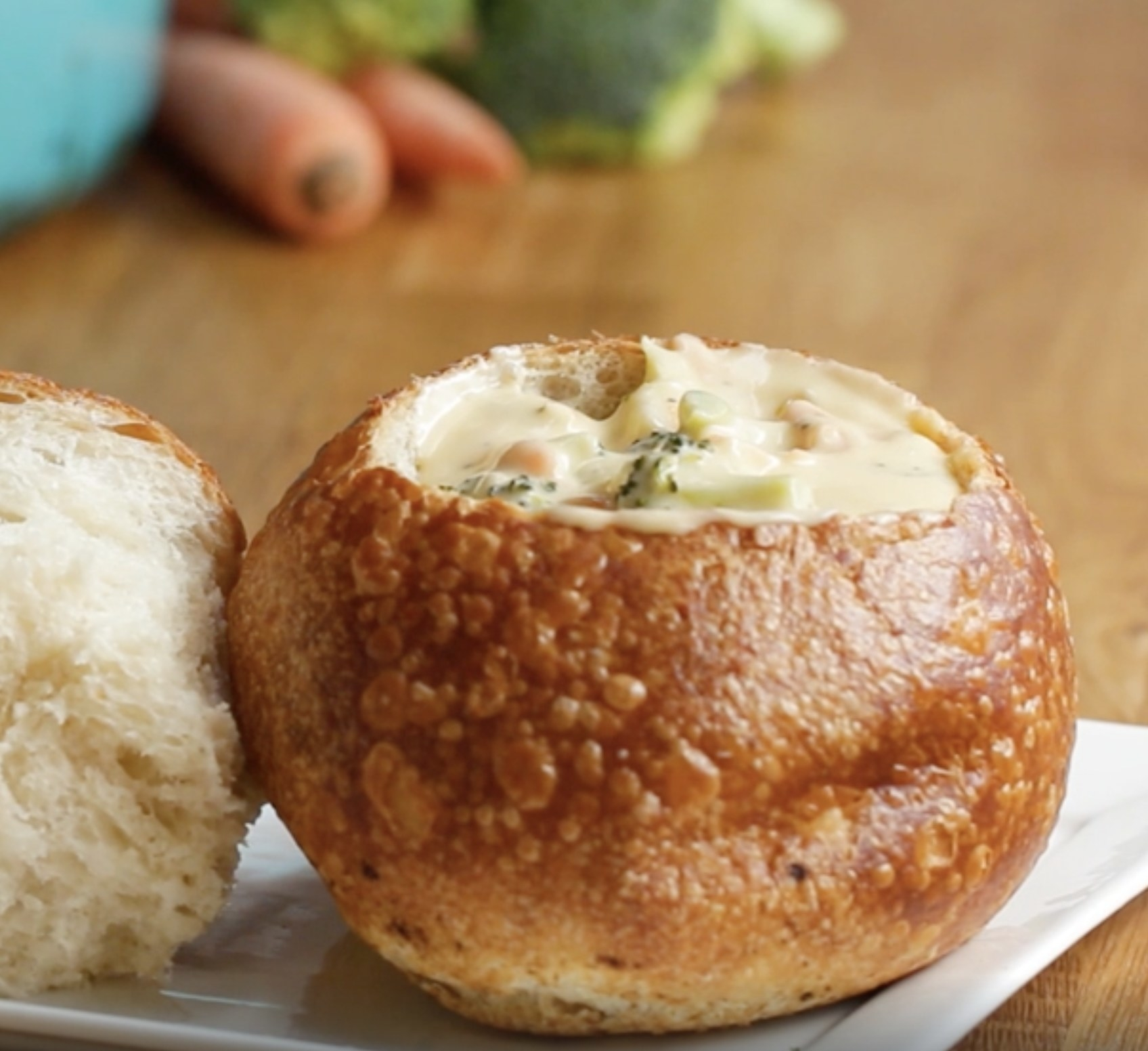 A bread bowl with broccoli cheddar soup inside