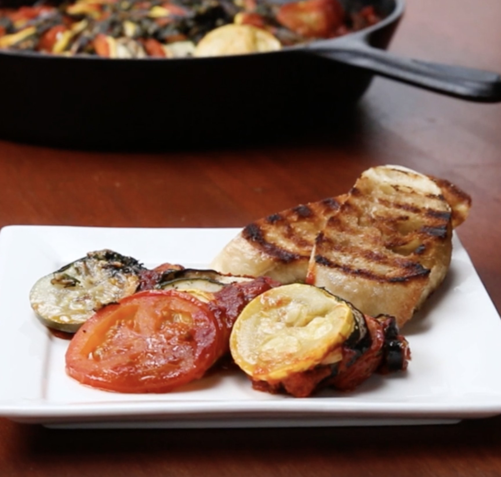 A dish of ratatouille with two slices of toasted french bread