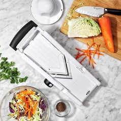 the mandoline slicer on a countertop with veggies
