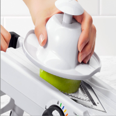 a hand slicing a vegetable using the gripper