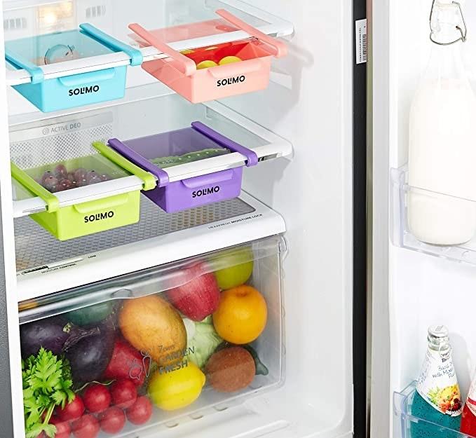 Multi coloured fridge organisers stacked on fridge shelves.