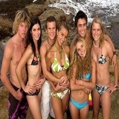 Full season 1 cast of Blue Water High in their swimwear by the beach
