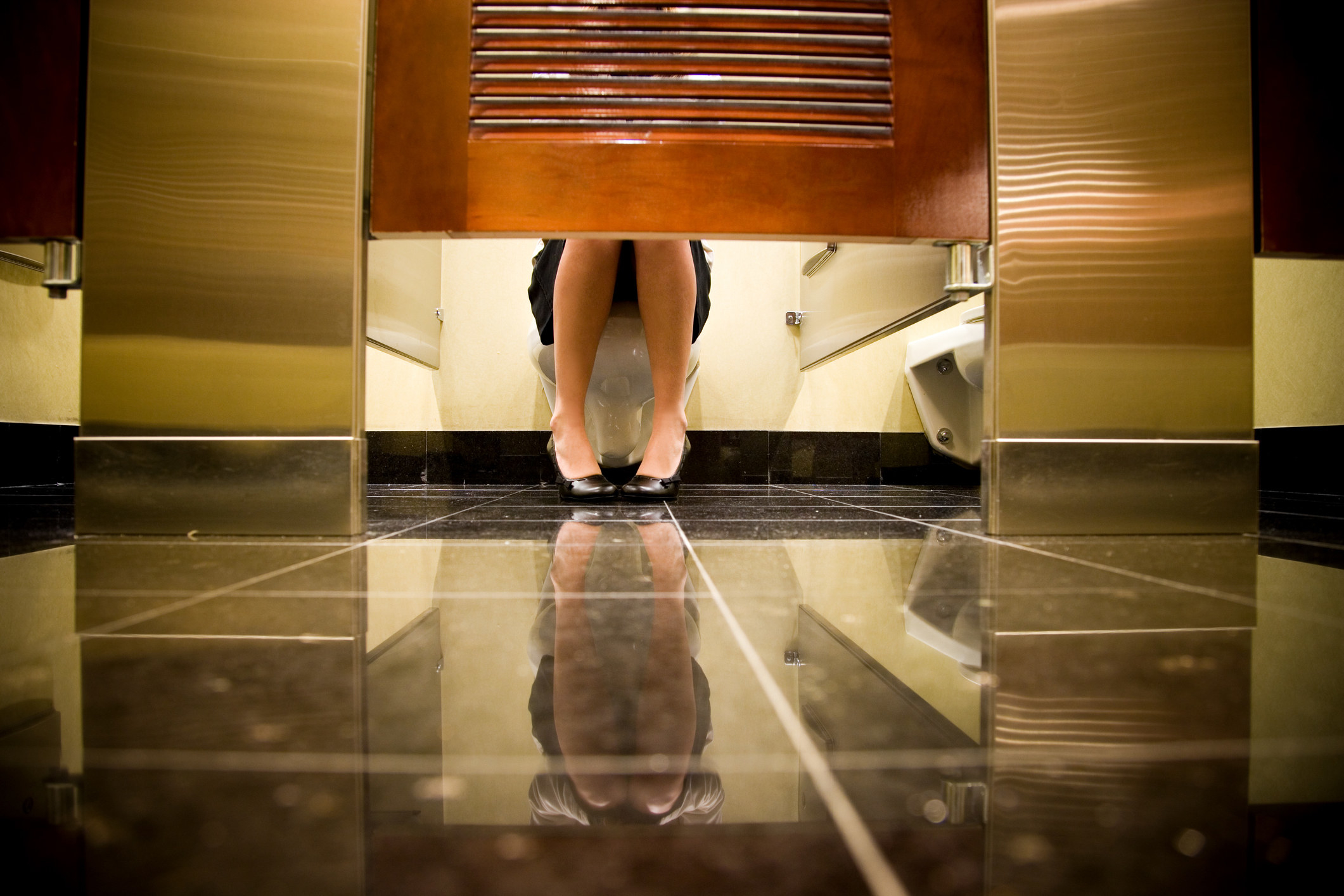 A woman in a public restroom stall