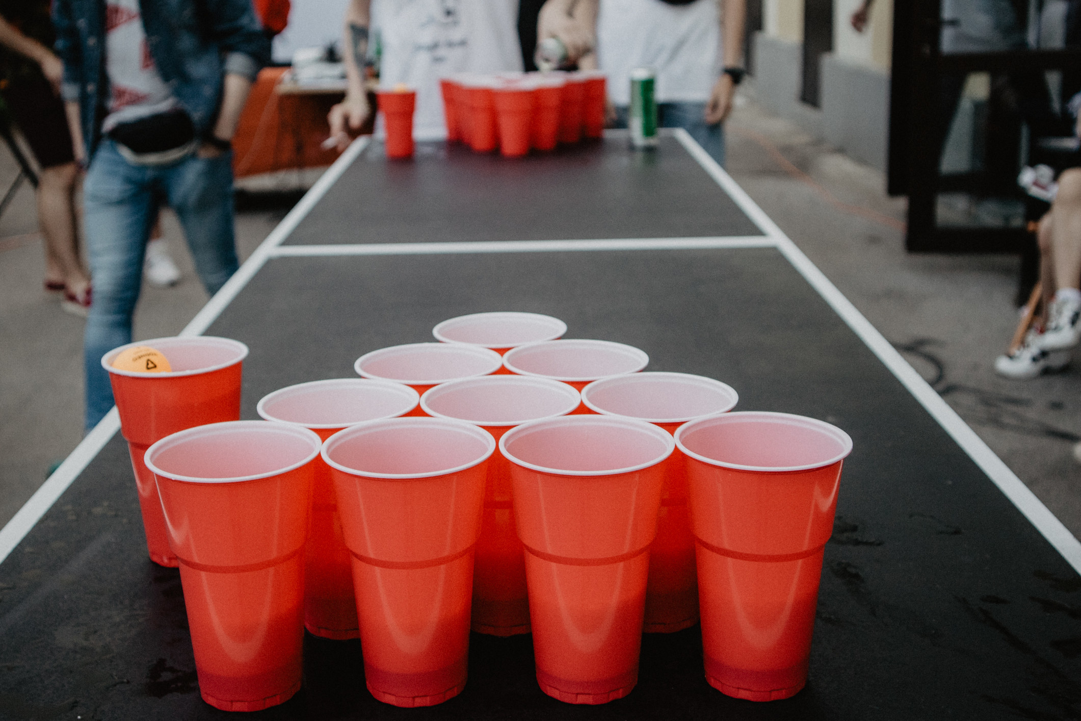 People playing a drinking game with red solo cups