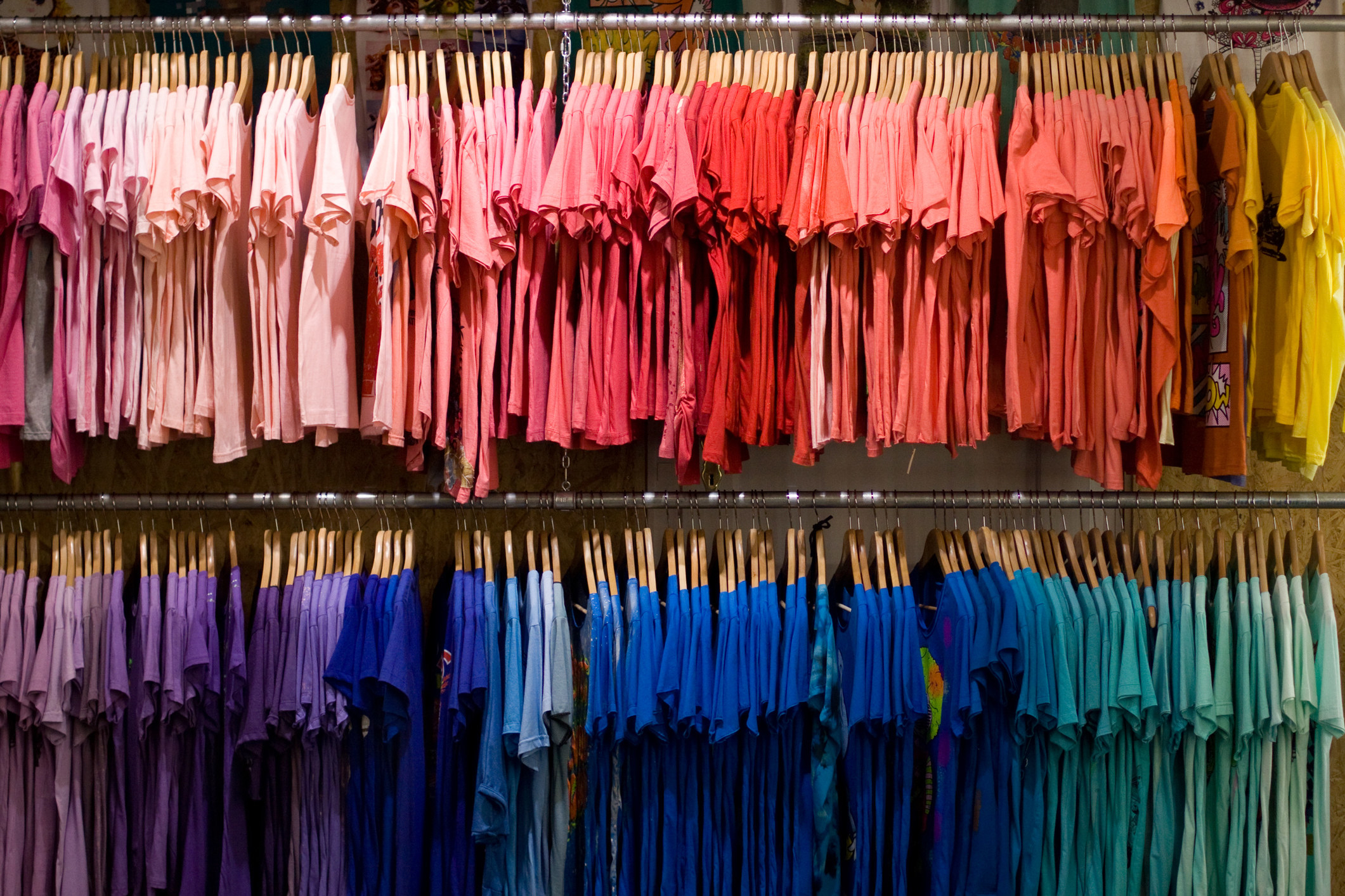 A rack of brightly colored T-shirts