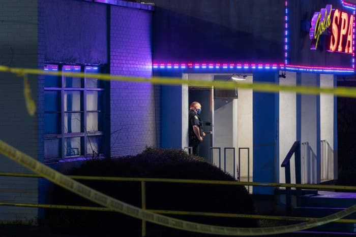 A police officer stands outside the entrance of a spa, where caution tape is hung up