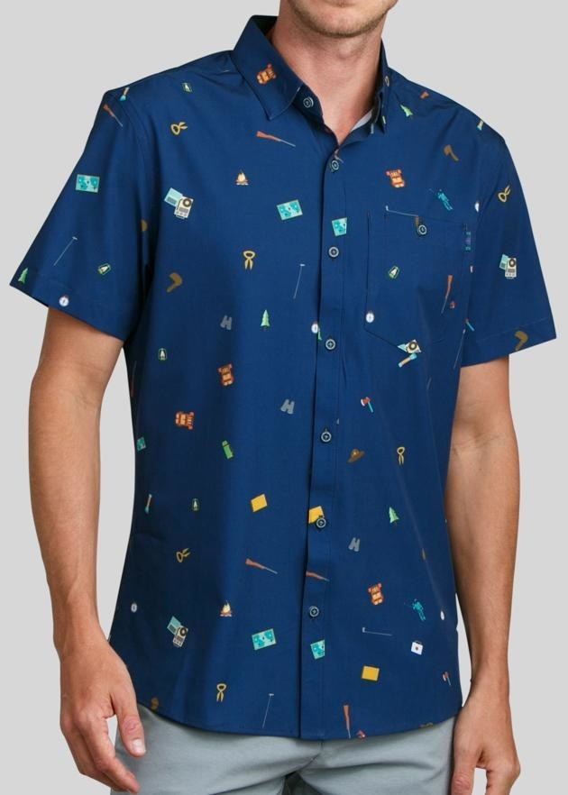 a model wearing a blue button down with icons from moonrise kingdom on it