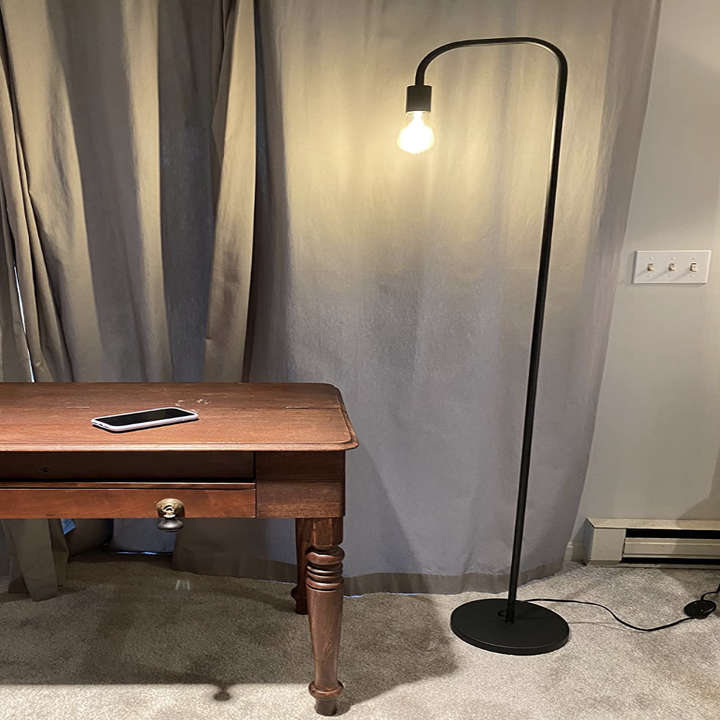 Black floor lamp with base and thin black arching neck in a study